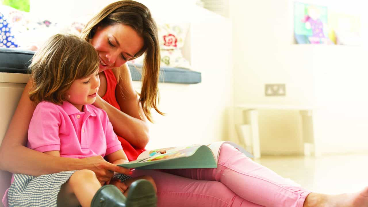 Woman reading to daughter in comfortable house